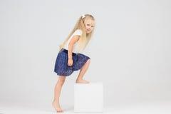逗人喜爱的矮小的白肤金发的女孩攀登白色立方体 库存照片