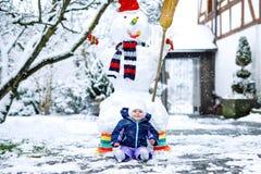 逗人喜爱的矮小的美丽的女婴在与雪和雪人的冬日 库存照片