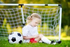 逗人喜爱的矮小的足球运动员伤害了她的膝盖,当保卫目标时 免版税库存图片