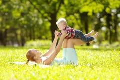 逗人喜爱的矮小的婴孩在有母亲的公园草的。甜bab 库存照片