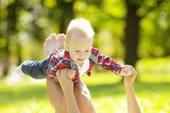 逗人喜爱的矮小的婴孩在有母亲的夏天公园草的。Swee 库存图片