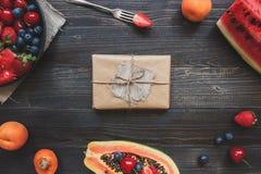 逗人喜爱的礼物盒包裹与工艺纸和夏天果子顶视图 夏天礼物 免版税库存照片