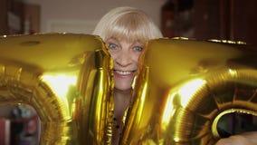 逗人喜爱的祖母庆祝她的生日 举行气球在她的手上 股票录像