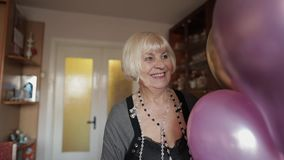 逗人喜爱的祖母庆祝她的生日 在她的手上拿着多彩多姿的气球 股票视频