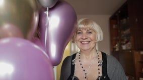 逗人喜爱的祖母庆祝她的生日 在她的手上拿着多彩多姿的气球 股票录像