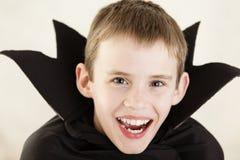 逗人喜爱的笑的吸血鬼男孩关闭  免版税库存图片
