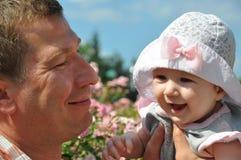 逗人喜爱的笑的婴孩和愉快的父亲画象 图库摄影