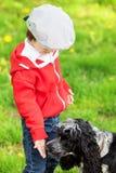 逗人喜爱的笑的男孩和他的狗,使用在公园,春天 免版税库存图片
