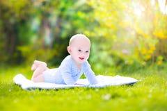 逗人喜爱的笑的婴孩在庭院里 免版税库存照片