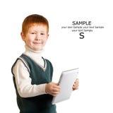 逗人喜爱的红发孩子站立与片剂个人计算机 隔绝在w 免版税图库摄影
