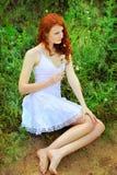 逗人喜爱的红头发人妇女用蒲公英 免版税库存照片