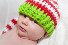 戴逗人喜爱的编织帽子的婴孩 免版税库存照片