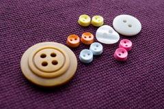逗人喜爱的缝合的爪牙 与爱白色心脏按钮的滑稽的字符 紫罗兰色纺织品背景 宏观看法,软的焦点 免版税库存图片