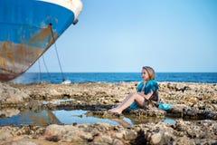 逗人喜爱的美丽的女孩坐在海岸海洋的岩石石头并且梦想看与在背景的一艘大被放弃的船 图库摄影