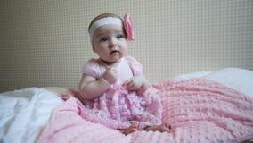 逗人喜爱的美丽的女婴坐在桃红色礼服的一张床 股票视频