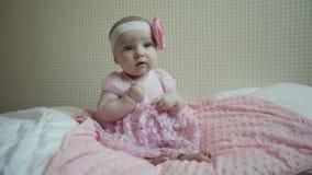 逗人喜爱的美丽的女婴坐在桃红色礼服的一张床 股票录像