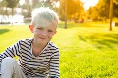 逗人喜爱的美丽的愉快的微笑的小男孩坐看照相机的草 库存照片