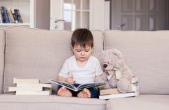 逗人喜爱的聪明的矮小的男婴敏锐关于看书在家坐有玩具熊玩具和堆的沙发书 免版税图库摄影