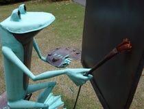 绘逗人喜爱的艺术家青蛙的雕象户外。 免版税库存照片