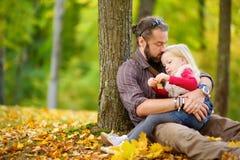 逗人喜爱的获得小女孩和她的父亲乐趣在美好的秋天天 使用在秋天公园的愉快的孩子 会集黄色秋天的孩子 免版税库存图片