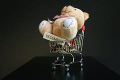 逗人喜爱的蓬松玩具熊和12月在有硬币的木棍子措辞写在深黑色背景的微型台车 免版税图库摄影