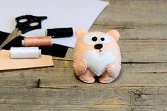 逗人喜爱的被充塞的玩具熊玩具 与心脏的玩具熊由毛毡制成 在木背景的工艺品材料 免版税库存图片