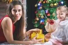 逗人喜爱的装饰圣诞树的婴孩和妈咪 红色的球 库存照片