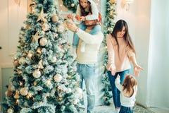 逗人喜爱的装饰自圣诞前夕的女孩和她的母亲冷杉木 免版税库存图片