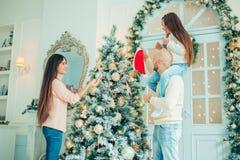 逗人喜爱的装饰自圣诞前夕的女孩和她的母亲冷杉木 库存图片