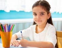 逗人喜爱的西班牙女孩文字在学校 免版税库存图片