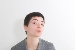 逗人喜爱的迷人的在照相机的短发妇女吹的空气亲吻在白色演播室背景 免版税图库摄影