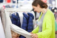 逗人喜爱的选择衣裳的小女孩和她的母亲在商店 免版税库存照片