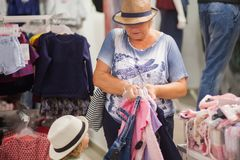逗人喜爱的选择衣裳的小女孩和她的祖母在商店 免版税库存照片