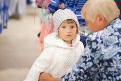 逗人喜爱的选择衣裳的小女孩和她的祖母在商店 库存图片