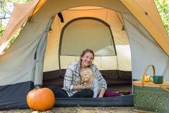 逗人喜爱的野营在帐篷的妈妈和女儿 免版税库存照片