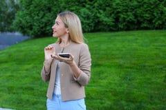 逗人喜爱的金发碧眼的女人在手上拿着电话,看并且微笑谜 免版税库存照片