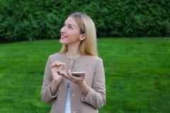 逗人喜爱的金发碧眼的女人在手上拿着电话,看并且微笑谜 图库摄影