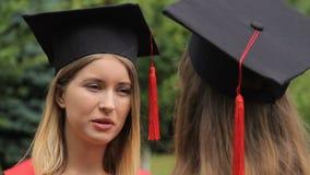 逗人喜爱的金发碧眼的女人毕业生谈话与最好的朋友和微笑,交谈,未来 股票视频
