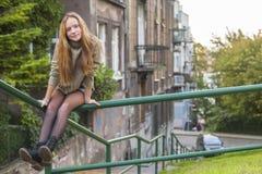 年轻逗人喜爱的长发女孩坐栏杆在老镇 结构 库存照片