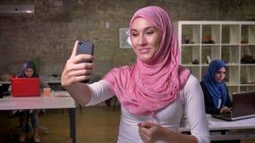 逗人喜爱的阿拉伯妇女是桃红色好的hijab有视频通话,当站立在砖现代室,在她工作的同事附近时 股票录像