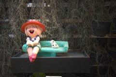 逗人喜爱的陶瓷逗人喜爱的微笑的女孩阅读书,当坐与黑小点白色狗时的长凳 免版税库存图片