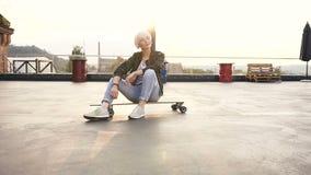 逗人喜爱的青少年的女孩坐她的屋顶现代大厦的滑板 年轻白肤金发的妇女坐longboarding 影视素材