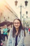 逗人喜爱的青少年的女孩穿过城市走 图库摄影