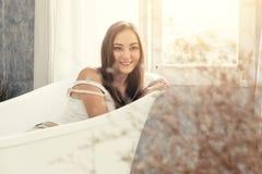逗人喜爱的青少年的妇女微笑的等待在浴缸 免版税图库摄影