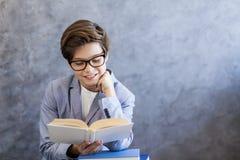 逗人喜爱的青少年的男孩阅读书 库存图片