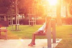 逗人喜爱的青少年的女孩在公园坐在日落 库存照片