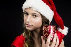 逗人喜爱的青少年的女孩在圣诞老人服装 图库摄影