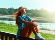 逗人喜爱的青少年的女孩坐江边 免版税库存照片