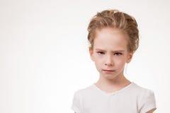逗人喜爱的青少年的女孩恼怒的皱眉,在白色背景隔绝的演播室画象 免版税库存照片