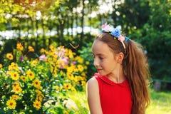 逗人喜爱的青少年的女孩是坐和作梦在温暖的太阳的庭院 免版税图库摄影